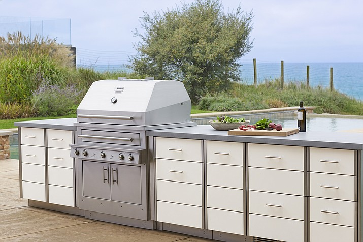 This photo provided by Kalamazoo Outdoor Gourmet of it's Hybrid (charcoal, wood and gas) professional grill and Arcadia series cabinetry is shown at a home in Michigan. Homeowners can add a rolling cart or other freestanding item for storage and food prep space outside. But adding a built-in cooking and storage space around a grill, as seen here, increases the value of a home. (Kalamazoo Outdoor Gourmet via AP)