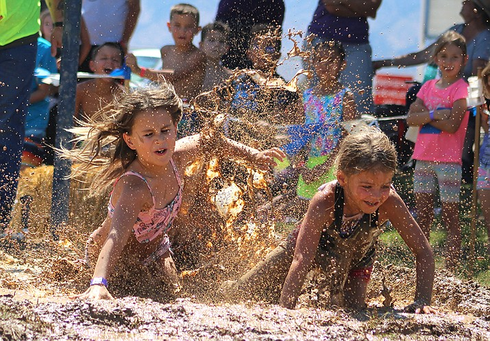 A pair of competitors take a dip in the mud Thursday during the 41st annual Mighty Mud Mania. (Photo by Beau Bearden/Daily Miner)