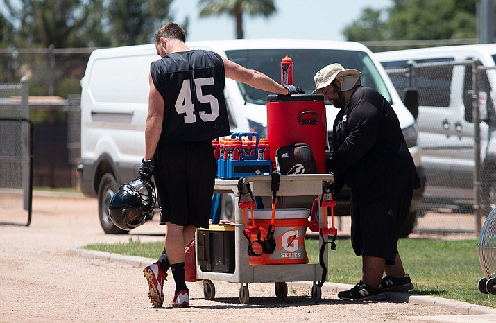 Because of the intense heat, Rattlers players, including linebacker Ryan Langford, take frequent water breaks during practice. (Photo by Matthew Andujo/Cronkite News)