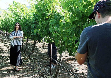 Yavapai College alumna Shanandoah Sterling poses in a Southwest Wine Center vineyard for a videographer producing a video for a national Phi Theta Kappa Marketing campaign.