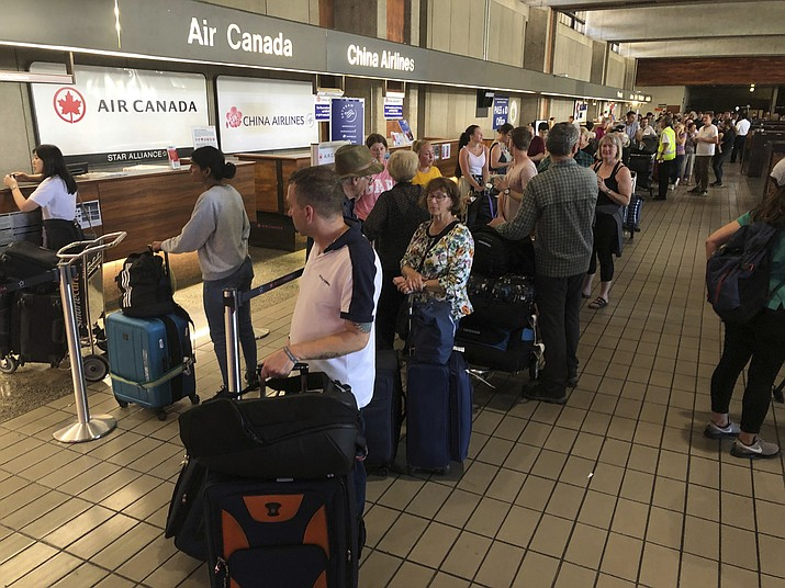 "Passengers from an Australia-bound Air Canada flight diverted to Honolulu Thursday, July 11, 2019, after about 35 people were injured during turbulence, stand in line at the Air Canada counter at Daniel K. Inouye International Airport to rebook flights. Air Canada said the flight from Vancouver to Sydney encountered ""un-forecasted and sudden turbulence,"" about two hours past Hawaii when the plane diverted to Honolulu. (Caleb Jones/AP)"