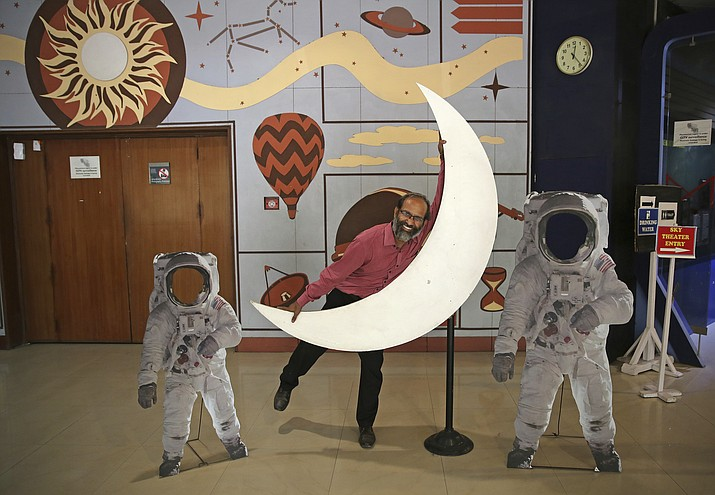 An employee playfully hugs a cut-out of a crescent moon at the Nehru Planetarium in New Delhi, India, Thursday, July 11, 2019. India is looking to take a giant leap in its space program and solidify its place among the world s spacefaring nations with its second unmanned mission to the moon, this one aimed at landing a rover near the unexplored south pole. (Altaf Qadri/AP)