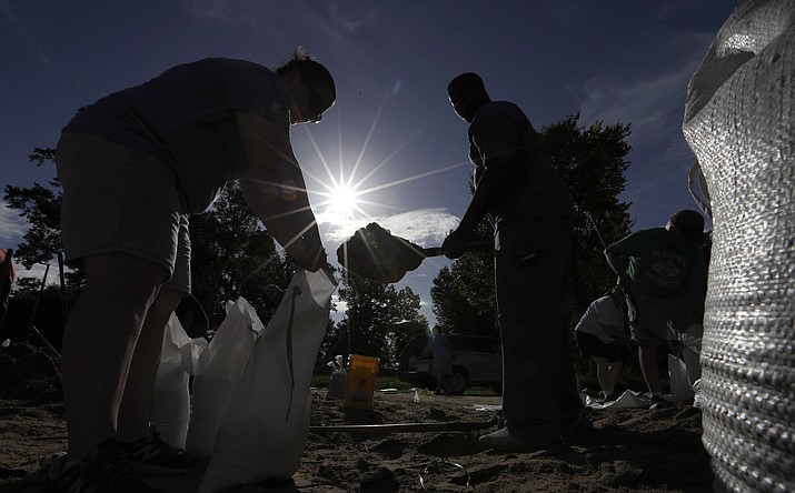 Residents fill sandbags Friday, July 12, 2019, in Baton Rouge, La., ahead of Tropical Storm Barry. The National Weather Service in New Orleans says water is already starting to cover some low lying roads in coastal Louisiana as Barry approaches the state from the Gulf of Mexico. (David J. Phillip/AP)