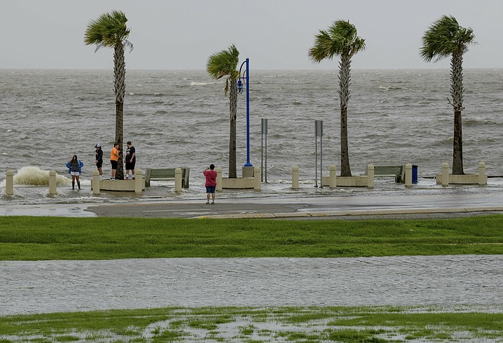 People check out the waves on Lakeshore Drive in New Orleans on Friday, July 12, 2019, as water moves in from Lake Pontchartrain from the storm surge from Tropical Storm Barry in the Gulf of Mexico. The area is behind a levee that protects the rest of the city. (Matthew Hinton/AP)