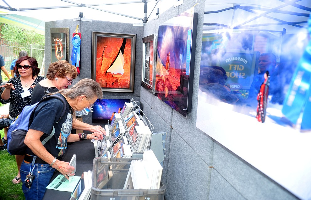Customers browse Priscilla Tacheny's artistic photographs at the Prescott Indian Arts Market at the Sharlot Hall Museum Saturday July 13, 2019. For a short video of the event go to dCourier.com..The show continues Sunday. (Les Stukenberg/Courier)