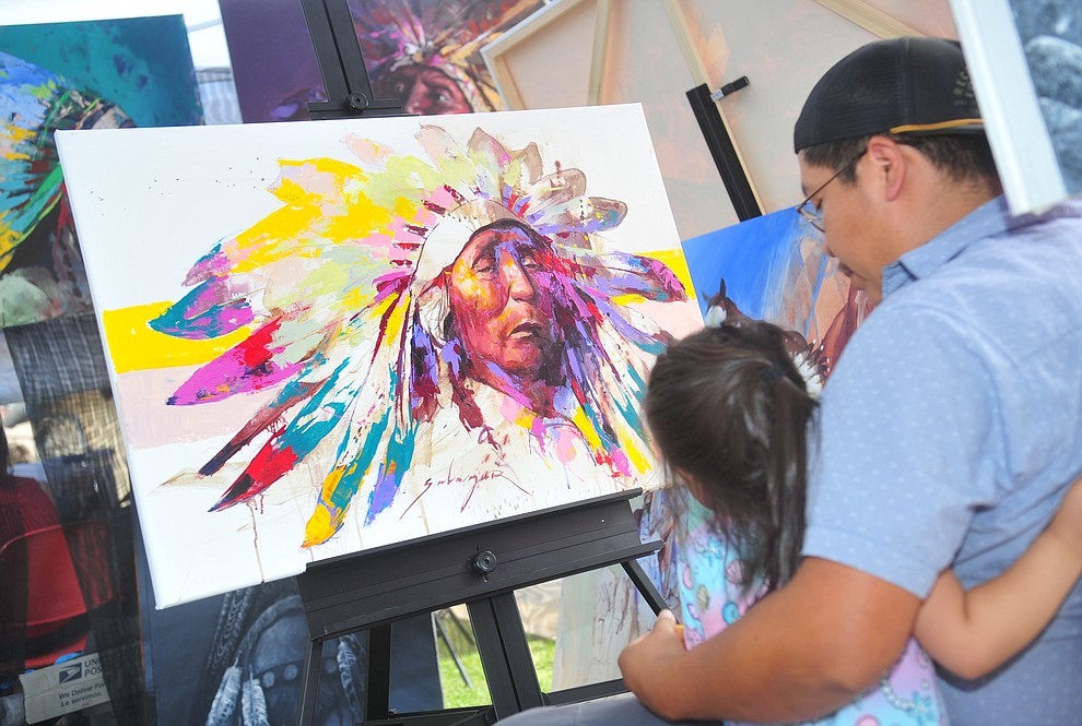 Navajo painter Jeremy Salazar looks at his most recent piece at the Prescott Indian Arts Market at the Sharlot Hall Museum Saturday July 13, 2019. For a short video of the event go to dCourier.com..The show continues Sunday. (Les Stukenberg/Courier)