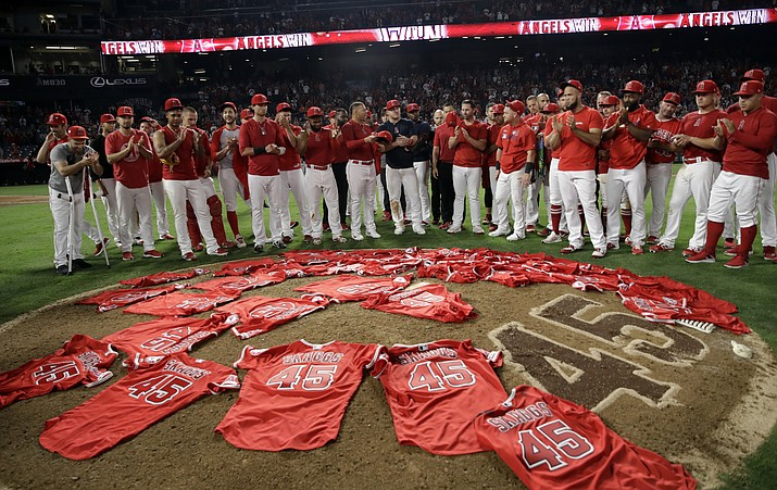 Members of the Los Angeles Angels place their jerseys with No. 45 in honor of pitcher Tyler Skaggs on the mound after a combined no-hitter against the Seattle Mariners during a game Friday, July 12, 2019, in Anaheim, Calif. The Angels won 13-0. (Marcio Jose Sanchez/AP)