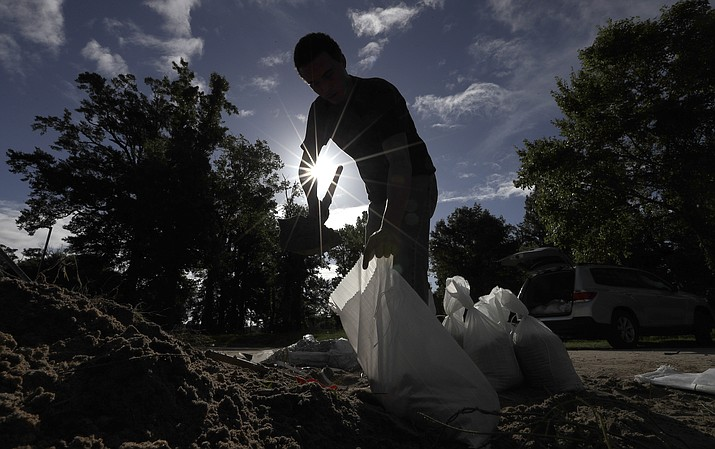 Chase Garces fills sandbags Friday, July 12, 2019, in Baton Rouge, La., ahead of Tropical Storm Barry. Barry could harm the Gulf Coast environment in a number of ways. But scientists say it is hard to predict how severe the damage will be. (David J. Phillip/AP)