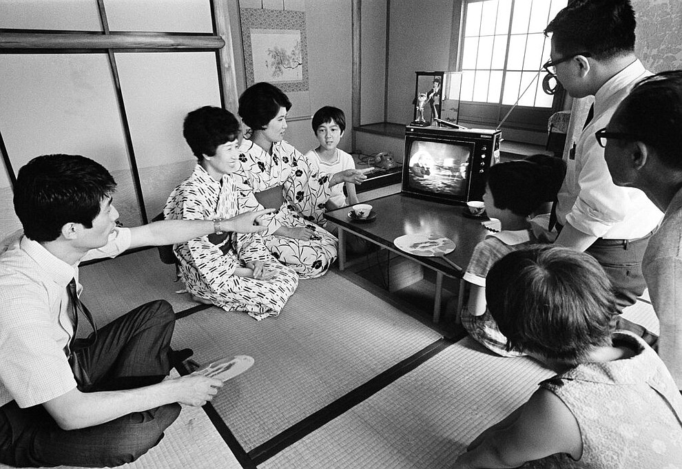 FILE - In this July 21, 1969 file photo, a family in Tokyo watches TV showing U.S. President Richard Nixon superimposed on a live broadcast of the Apollo 11 astronauts saluting from the moon. (AP Photo)