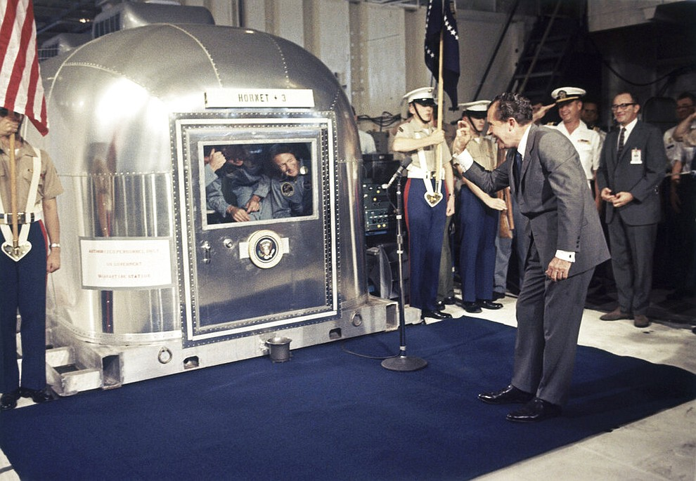 """FILE - In this July 24, 1969 file photo, President Richard Nixon gives an """"OK"""" sign as he greets Apollo 11 astronauts Neil Armstrong, Michael Collins, and Buzz Aldrin in a quarantine van aboard the USS Hornet after splashdown and recovery in the Pacific Ocean. (AP Photo)"""