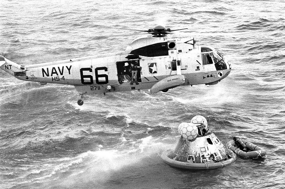 In this July 24, 1969 photo from the U.S. Navy, Navy UDT swimmer Clancy Hatleberg prepares to jump from a helicopter into the water next to the Apollo 11 capsule after it splashed down in the Pacific Ocean, to assist the astronauts into the raft at right. (Milt Putnam/U.S. Navy via AP)