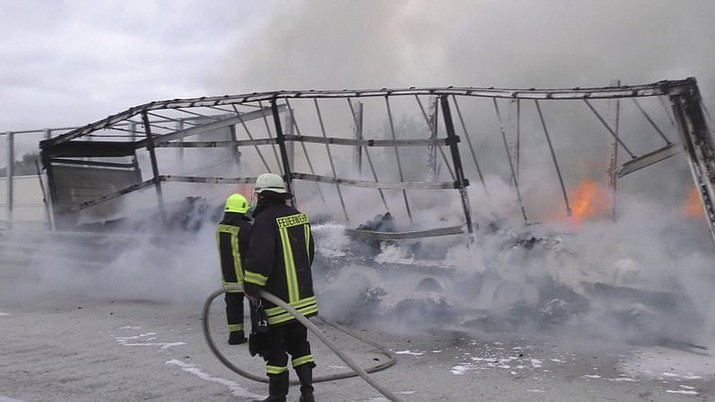 Firefighters attend the scene after a cocoa-laden truck trailer set on fire on the A14 autobahn near Grabow, Germany, Monday, July 15, 2019. German authorities say a busy stretch of highway had to be shut down after a transport truck carrying 17 tons of cocoa caught fire. They say the driver escape unharmed but all of the cocoa was destroyed in the flames. (dpa via AP)
