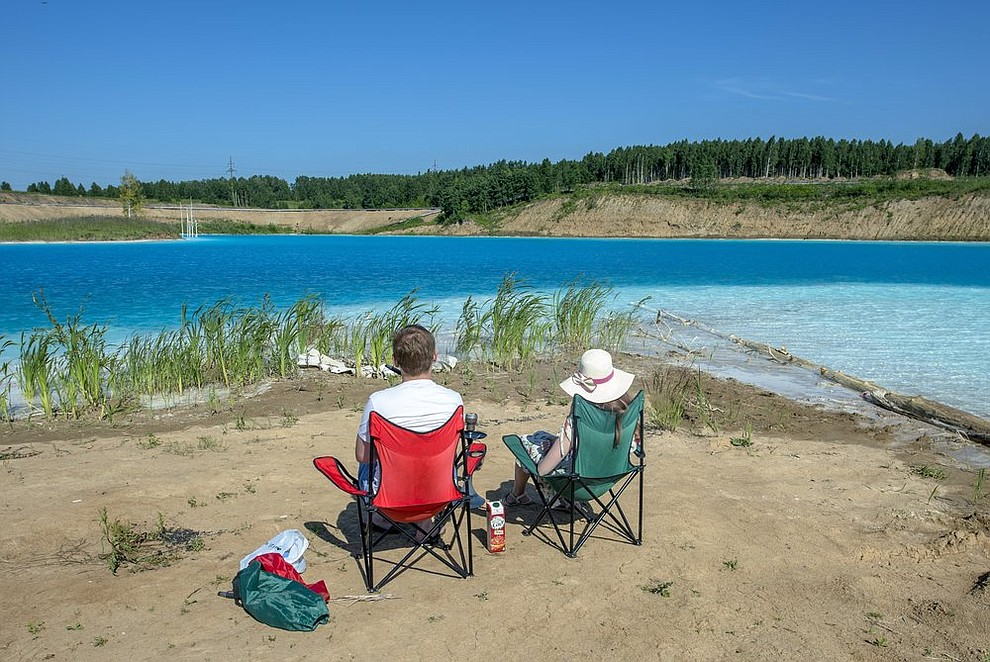 In this Friday, July 12, 2019 photo, a couple sit by a lake in the Siberian city of Novosibirsk, about 2,800 kilometers (1,750 miles) east of Moscow, Russia. (AP Photo/Ilnar Salakhiev)