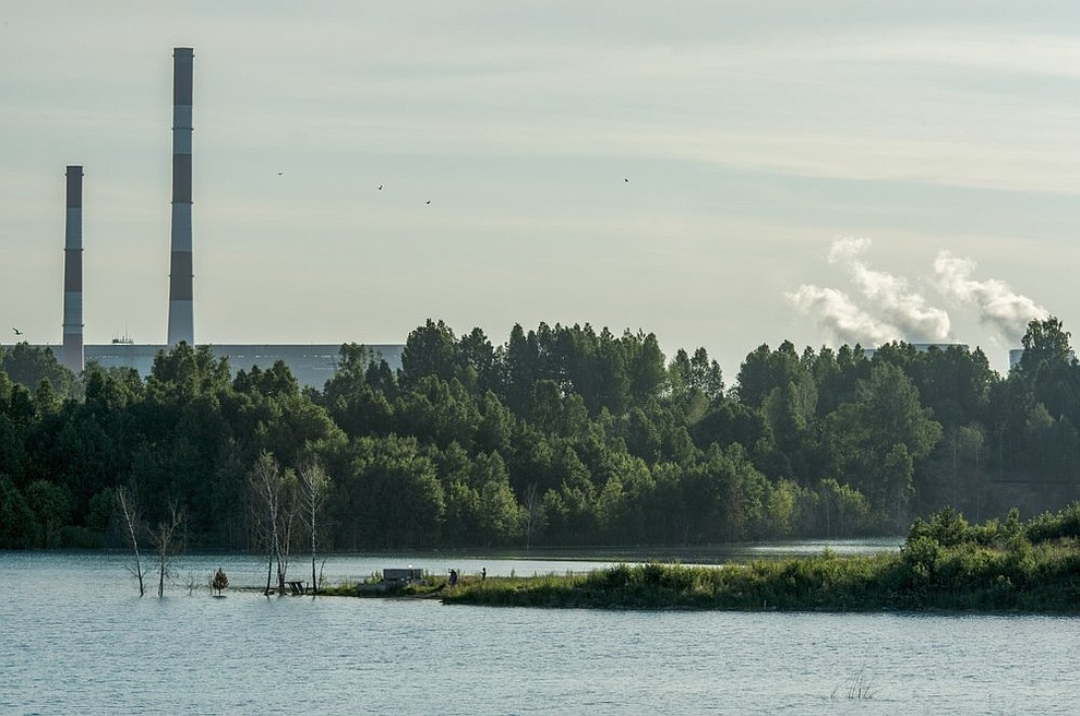 In this photo taken on Friday, July 12, 2019, a view of a lake and a power station in the background are seen in the Siberian city of Novosibirsk, about 2,800 kilometers (1,750 miles) east of Moscow, Russia. (AP Photo/Ilnar Salakhiev)