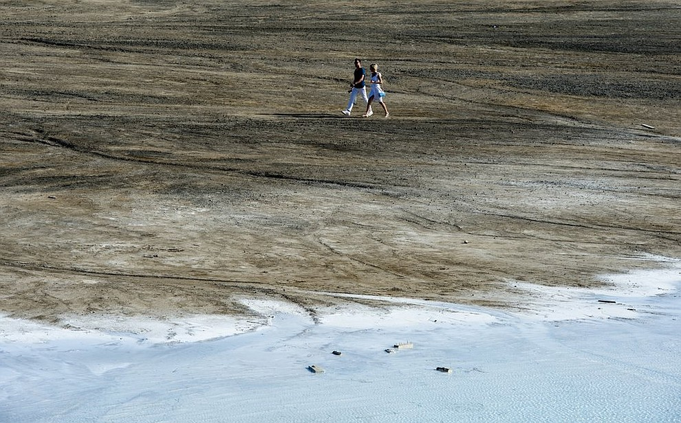 In this Friday, July 12, 2019 photo, a couple walk by a lake in the Siberian city of Novosibirsk, about 2,800 kilometers (1,750 miles) east of Moscow, Russia. (AP Photo/Ilnar Salakhiev)