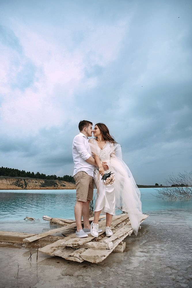 In this handout photo taken by ekaterinaaaaks on Sunday, June 23, 2019, a newlywed couple pose for a photo by a lake and a power station in the background are seen in the Siberian city of Novosibirsk, about 2,800 kilometers (1,750 miles) east of Moscow, Russia. (ekaterinaaaaks via AP)