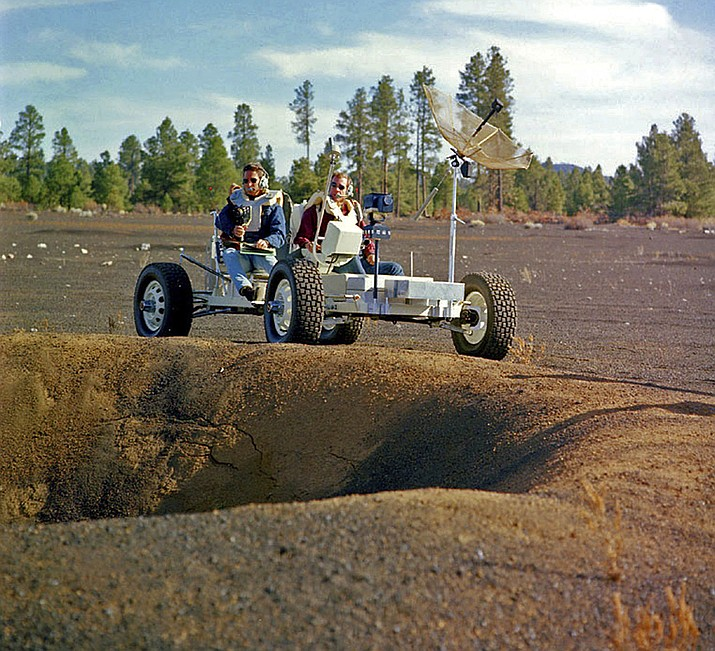 Apollo 15 astronauts Jim Irwin, left, and Dave Scott driving a prototype of a lunar rover in a volcanic cinder field east of Flagstaff, Arizona. The rover, named Grover, now is on display at the science center. (U.S. Geological Survey Astrogeology Science Center via AP)