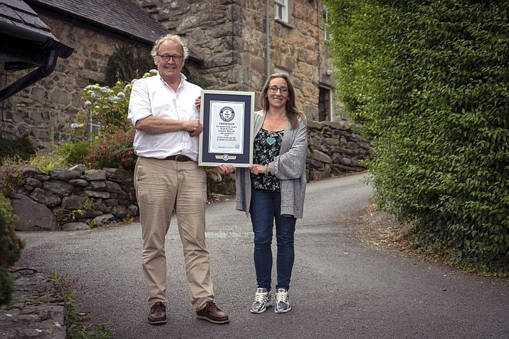 In this undated handout photo provided by Guinness World Records on Tuesday, July 16, 2019, Gwyn Headley and Sarah Badhan, stand on Ffordd Pen Llech with a certificate from Guinness World Records, confirming that the road is the steepest street in the world, in the seaside town of Harlech, North Wales. A street in Wales has been designated the steepest in the world after a successful campaign by local residents. The title comes at the expense of a street in New Zealand which has been eclipsed in the steepness sweepstakes. The Welsh campaign was led by businessman and architectural historian Gwyn Headley. (Andrew Davies/Guinness World Records via AP)