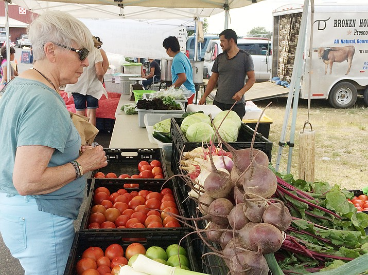 Linda Gould checks out some produce from Hernandez Farm at the Chino Valley Farmers Market Thursday, July 11, 2019. (Jason Wheeler/Review)