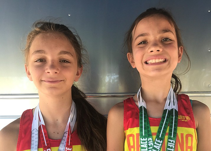 Mia Fisher, left, and younger sister Lyla Fisher of the Prescott Flyers show off their medals after competing at the USATF Region 10 Championships for the Junior Olympics from July 4-7 at Mesa Community College. (Derek Fisher/Courtesy)