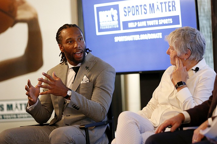 NFL player Larry Fitzgerald, left, and Senior Director of Research and programs at The Women's Sports Foundation, Dr. Marjorie Snyder, serve as panelists at the DICK'S Sports Matter Panel Event on Thursday, July 18, 2019, in New York. (Jason DeCrow/AP Images for DICK'S Sporting Goods, File)