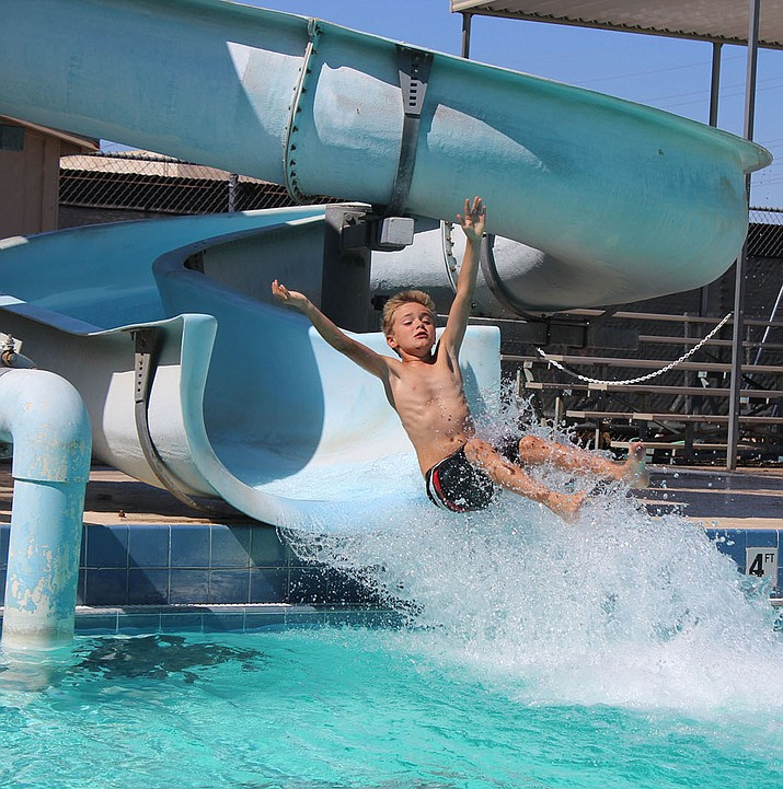Braden Gant launches out of the slide at Centennial Pool. He was among a number of children beating the heat with a dip in the water. (Photo by Beau Bearden/Daily Miner)