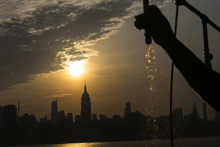 The sun rises over New York City and the Empire State Building while a man sprays water at Pier A on Saturday, July 20, 2019 in Hoboken, N.J. Temperatures in the high 90s are forecast for Saturday and Sunday with a heat index well over 100. Much of the nation is also dealing with high heat. (Eduardo Munoz Alvarez/AP)