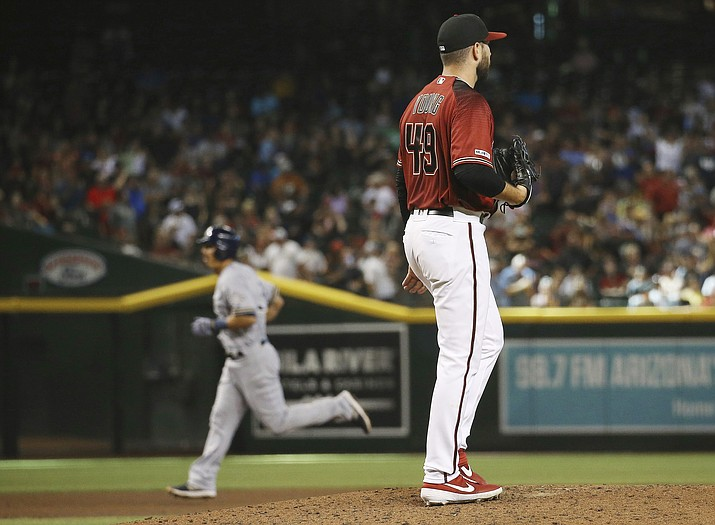 Arizona Diamondbacks starting pitcher Alex Young (49) pauses on the mound after giving up a grand slam to Milwaukee Brewers' Tyler Saladino, left, during the fourth inning of a baseball game Sunday, July 21, 2019, in Phoenix. (Ross D. Franklin/AP)