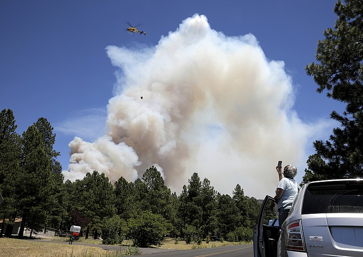 A helicopter carries a bucket of water to attack hot spots on the Museum Fire in Flagstaff, Ariz., Sunday, July 21 2019. (Jake Bacon/Arizona Daily Sun via AP)