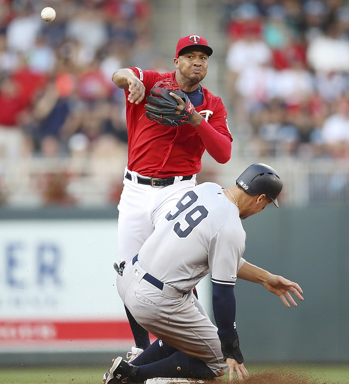 Minnesota Twins second baseman Jonathan Schoop, top, throws to first to complete a first-inning triple play after forcing out New York Yankees' Aaron Judge (99) during a baseball game Monday, July 22, 2019, in Minneapolis. (Jeff Wheeler/Star Tribune via AP)