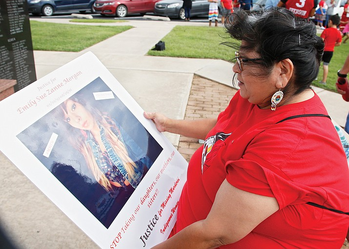 In this June 14 photo, Carmen Thompson, of El Reno, Okla., looks over a poster of her niece Emily Morgan who was murdered in 2016, before the start of a march to call for justice for missing and murdered indigenous women at the Cheyenne and Arapaho Tribes of Oklahoma in Concho, Okla. U.S. Senate staffers say officials missed a second deadline July 8 to offer input on bills on Native American safety, and only one department has since provided partial comment. (AP Photo/Sue Ogrocki, File)
