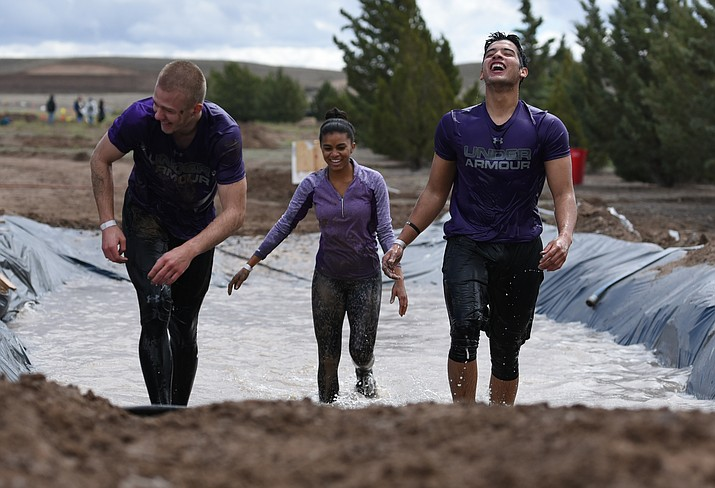 Joseph Keller, Caitlyn Ballard and Brandon Celaya laugh after the final obstacle during the 2018 Chino Mudder that is part of the Extreme Spring Fling in Chino Valley. (Les Stukenberg/Review, file)
