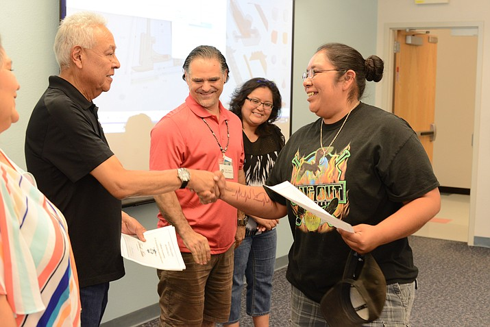 Hayes Lewis shakes hands with Tina Bowannie of Zuni, New Mexico after Bowannie earned a certificate for completing a two-day workshop on 3D printing. As part of the workshop, Bowannie was able to model a balloon-powered car and a two story house. (Photo/Navajo Technical University)