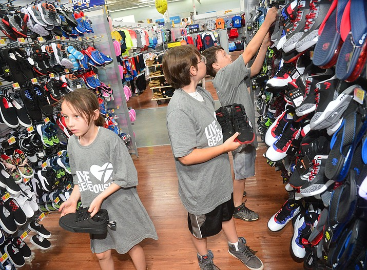 Halie, Brandon and Kameron Couch find shoes as Trinity Lutheran Church in Prescott Valley brought almost 20 Humboldt Elementary School students and their families to Walmart for a back-to-school clothing shopping trip Saturday, July 20, 2019. (Les Stukenberg/Courier)