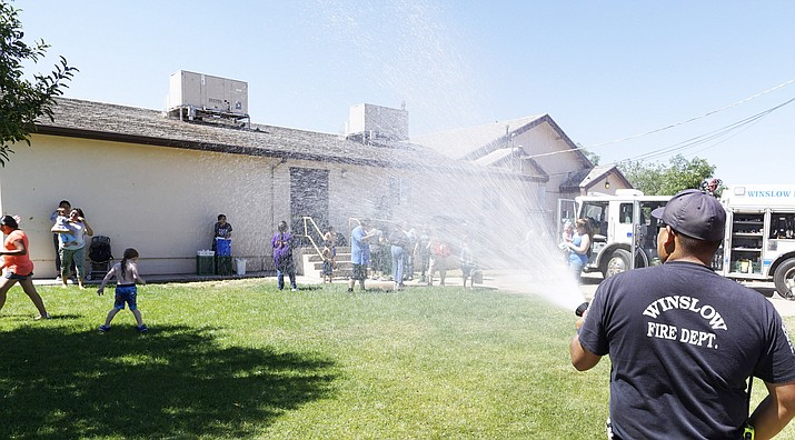 """Children play in the """"rain"""" from a Winslow Fire Department engine during an open house for first responders in Winslow July 9. (Todd Roth/NHO)"""