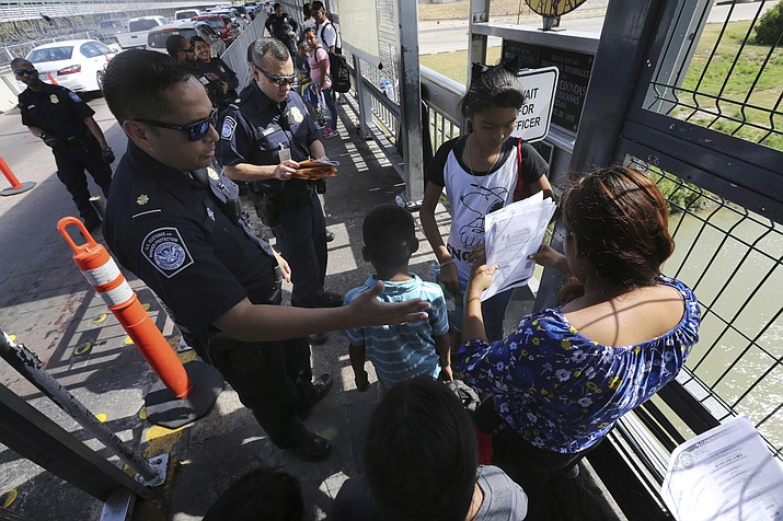 FILE - In this July 17, 2019, file photo, a United States Customs and Border Protection Officer checks the documents of migrants before being taken to apply for asylum in the United States, on International Bridge 1 in Nuevo Laredo, Mexico. On Wednesday, July 24, 2019, a federal judge in San Francisco will hear arguments in a challenge to the new Trump Administration policy that requires asylum-seekers who cross through a third country headed to the U.S. to first apply for protection in that other country. The lawsuit was brought by the American Civil Liberties Union, Southern Poverty Law Center, and Center for Constitutional Rights as they seek a temporary restraining order to block the plan. (AP Photo/Marco Ugarte, File