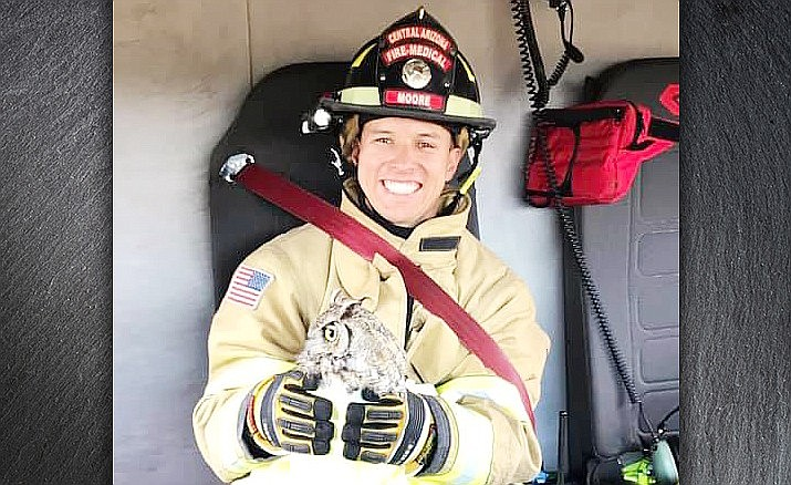 Central Arizona Fire and Medical Authority firefighter Aaron Moore holds an owl that he and several other firefighters rescued in Prescott Valley on July 10. Moore was burned while mopping up a mulch fire in Camp Verde on Sunday, July 21. (CAFMA/Courtesy)