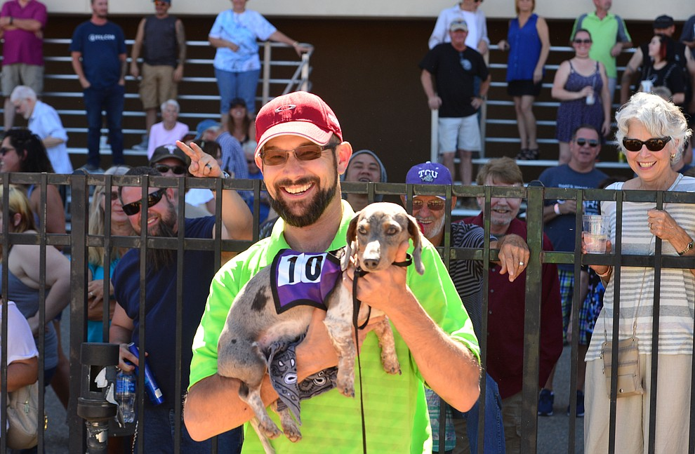 Devin Radell holds Loki the winner of the first heat of weiner dog racing at Arizona Downs in Prescott Valley Saturday July 20, 2019. (Les Stukenberg/Courier)