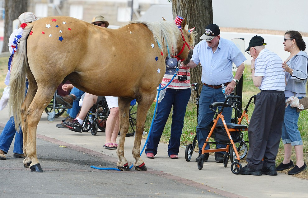 Harley greets Korean War veterans Lars Dohm and Jim Sutton after the Prescott Long Riders rode through the VA Hospital in Prescott Saturday July 27, 2019. (Les Stukenberg/Courier)