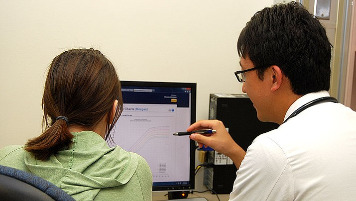 A doctor and a patient consult at the University of Michigan Medical School. A report says the U.S. health system is now covering 9 out of 10 people. (University of Michigan Medical School photo)