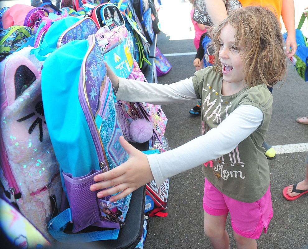 Prescott Valley's Aaliyah Payne finds her Frozen backpack as the Yavapai Food Bank gave away 1300 backpacks in the parking lot of Findlay Toyota Center Saturday July 27, 2019 in Prescott Valley. (Les Stukenberg/Courier)