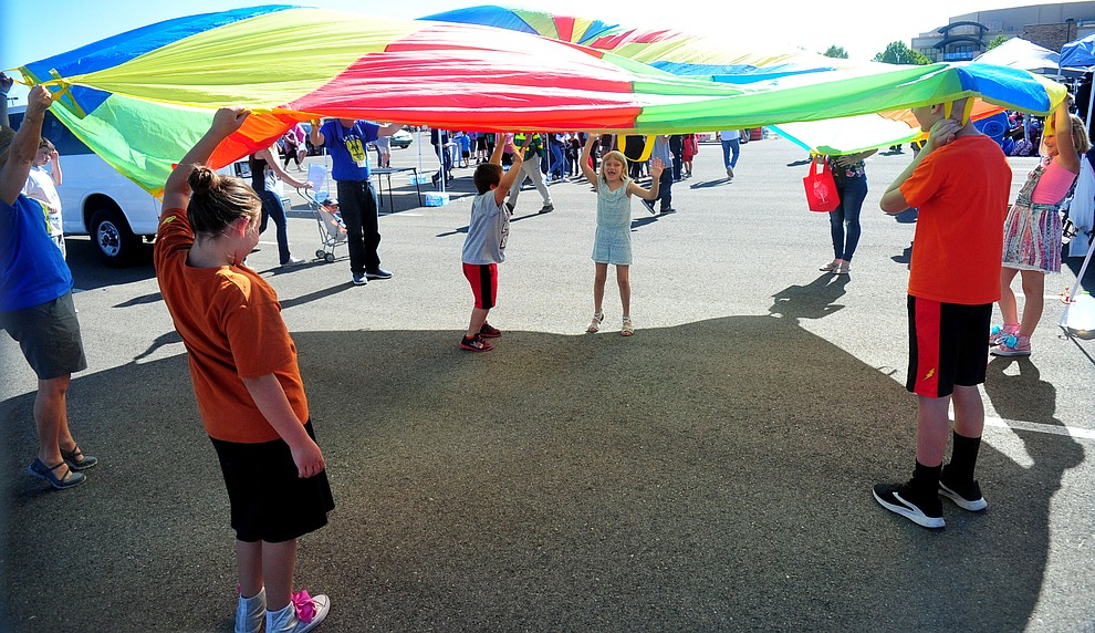 Kids play under a parachute as the Yavapai Food Bank gave away 1300 backpacks in the parking lot of Findlay Toyota Center Saturday July 27, 2019 in Prescott Valley. (Les Stukenberg/Courier)