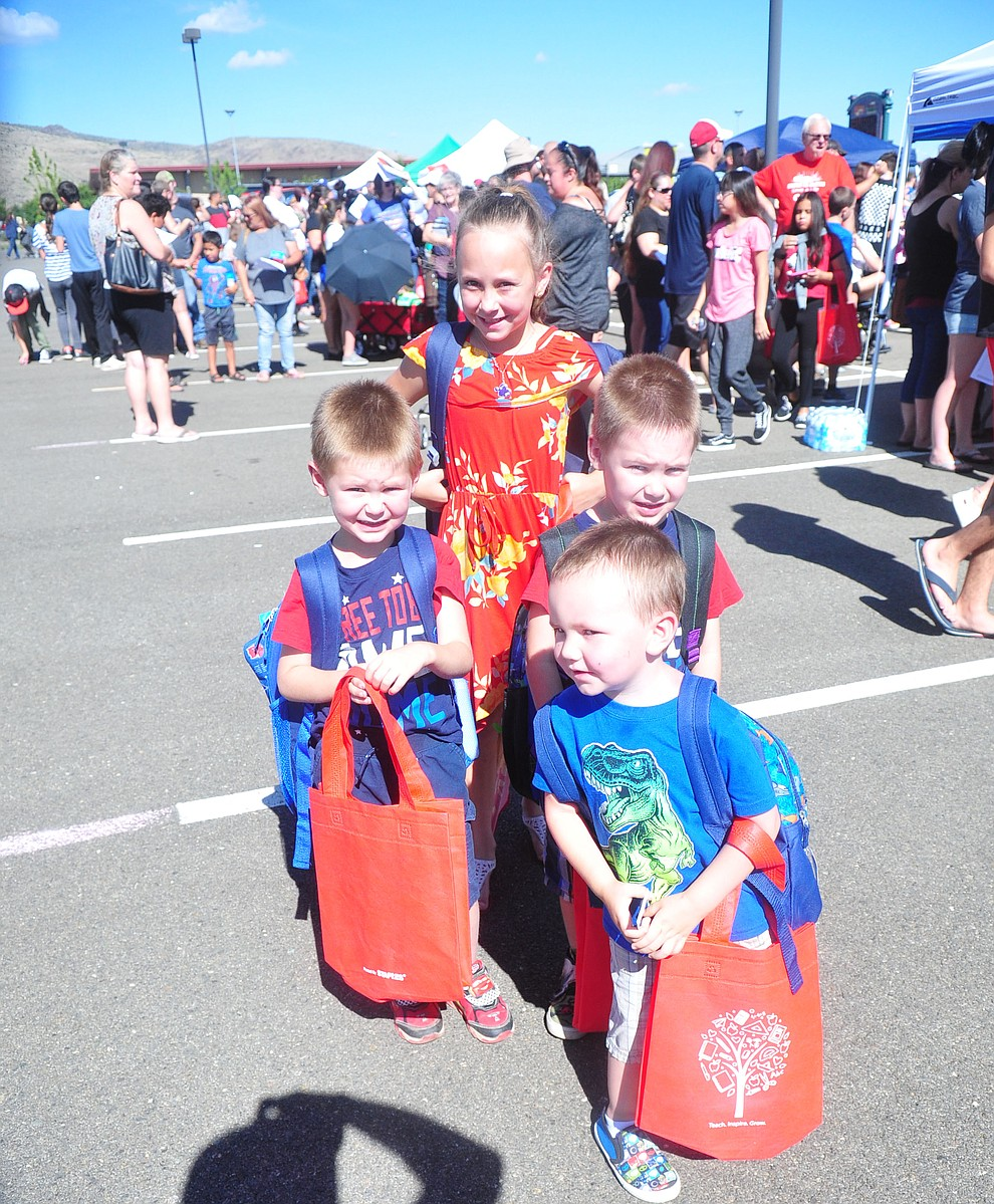 Chino Valley's Mason Parker, Zakary Parker, Brayden Parker and Kaylee Hannah all got their backpacks as the Yavapai Food Bank gave away 1300 backpacks in the parking lot of Findlay Toyota Center Saturday July 27, 2019 in Prescott Valley. (Les Stukenberg/Courier)