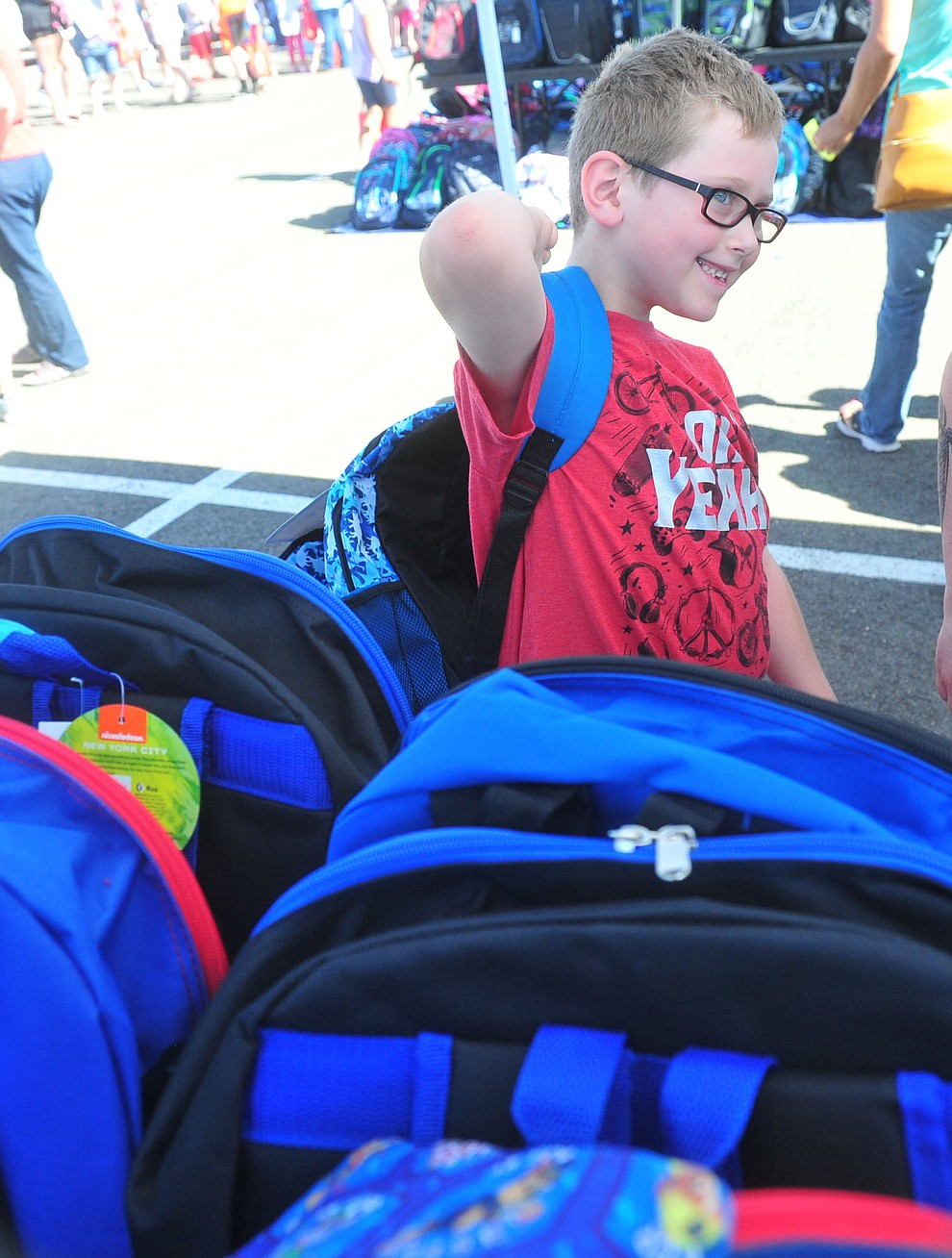 Darren Martinez is all smiles after getting his bacpack as the Yavapai Food Bank gave away 1300 backpacks in the parking lot of Findlay Toyota Center Saturday July 27, 2019 in Prescott Valley. (Les Stukenberg/Courier)