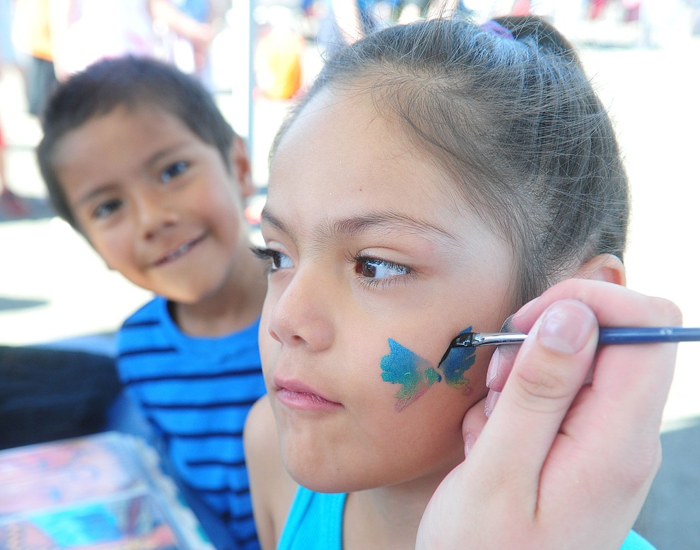 Frank S. watches as his sister Mia gets her face painted as the Yavapai Food Bank gave away 1300 backpacks in the parking lot of Findlay Toyota Center Saturday July 27, 2019 in Prescott Valley. (Les Stukenberg/Courier)