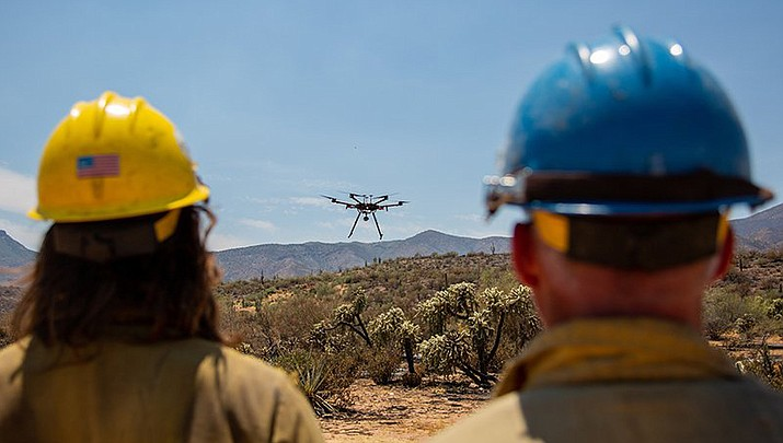 Pilot Chris Mariano (left, with aviation manager Gary Baumgartner) lands a Matrice 600 drone near the Woodbury fire in June. (Photo by Anton L. Delgado/News21 via Cronkite News)