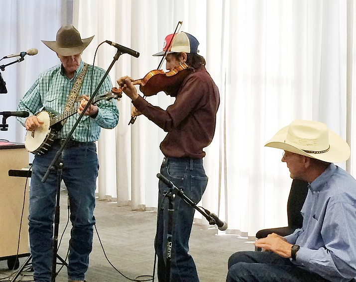 Joe Konkel and Friends play to a packed room in the Prescott Valley Public Library on Tuesday, July 23, during a Cowboy Poets Gathering presentation. From left are Konkel on banjo, Paulden; Jordan Brambila, on fiddle, Paulden; and Tom Walker playing spoons, Prescott. (Sue Tone/Review)