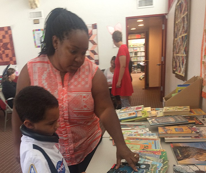 Ebony Smith and her son, Ayden Smith, look at which books to get during the character-con session of the Summer Fun Kids Club Wednesday, July 24, 2019. (Jason Wheeler/Review)