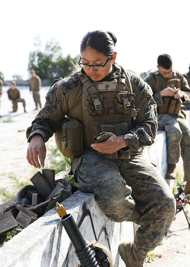 Leondra Begay, a 22-year-old female combat soldier in the U.S. Marine Corps loads her rifle magazine during training exercises with her combat unit. (Photo via Indian Country Today)