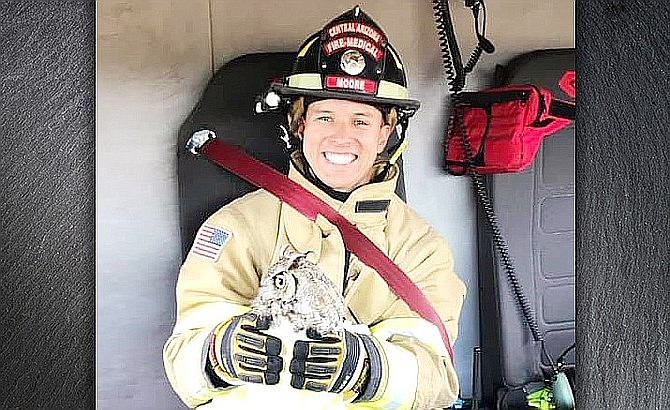 Aaron Moore holds an owl that he and several other firefighters rescued in Prescott Valley on July 10. (CAFMA/Courtesy)